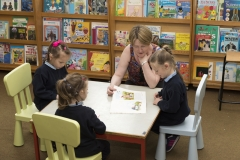 PRIMARY STUDENTS READING IN LIBRARY
